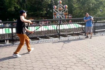 Mladý muž, který v New Yorku turistům stříhá selfie tyče